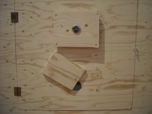 Puerta trasera, con mirilla y agujero, con tabla desplazable, para aportar la comida